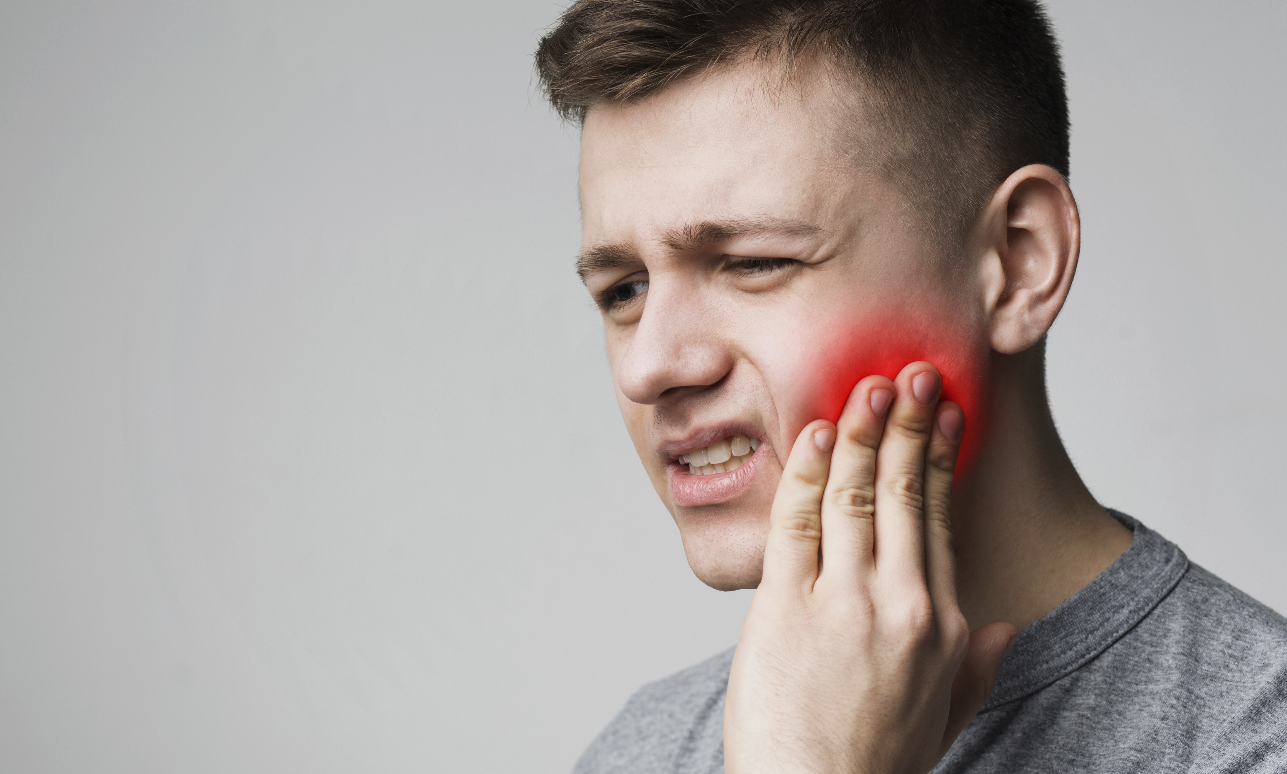 man touching jaw and grimacing