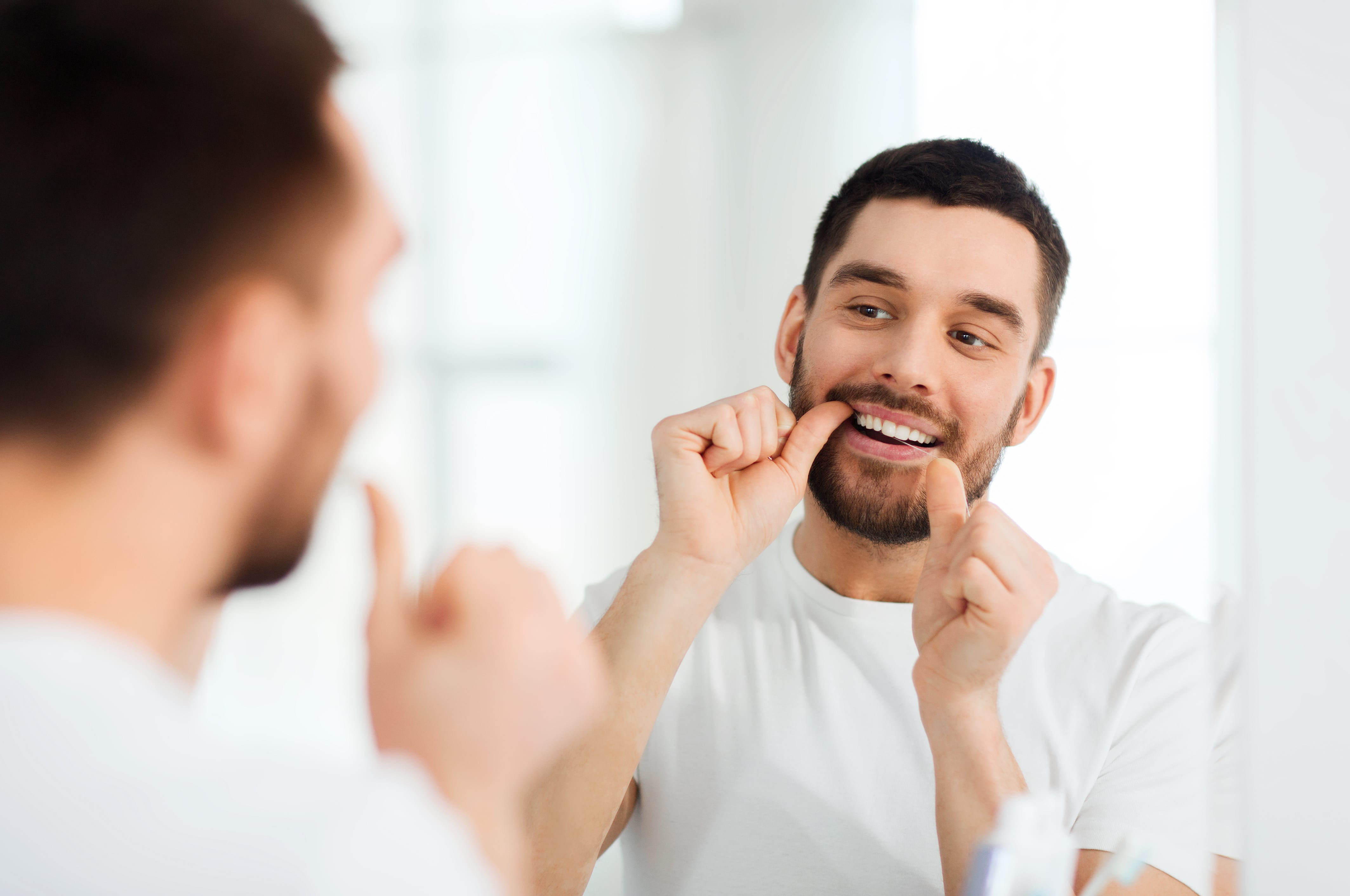 man looking in the mirror and flossing his teeth