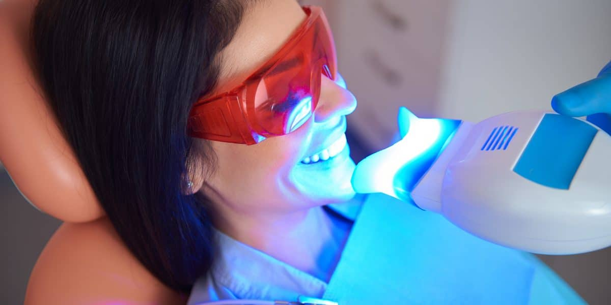 woman getting teeth whitened at dentist office